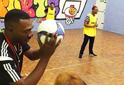 Young people playing basketball indoors at Concord youth centre in Hackney