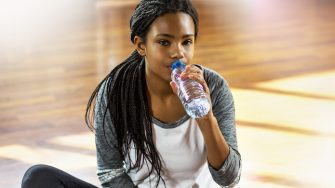 Young girl sitting and drinking water in a gym.